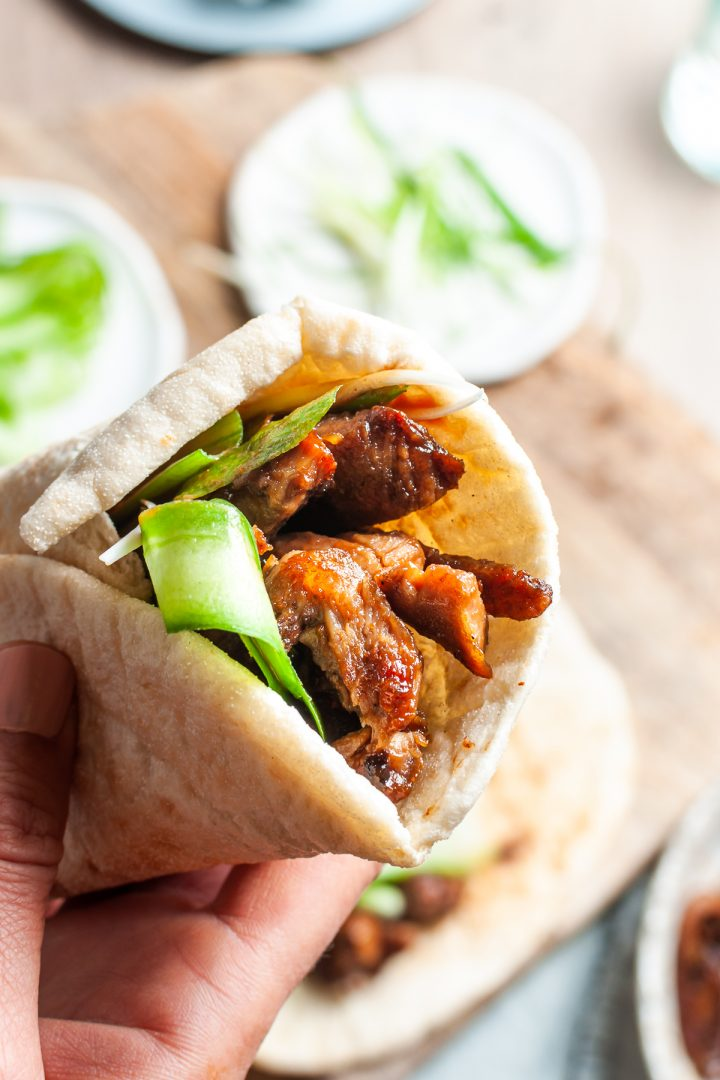 close up of folded lamb wrap being held, to show the juicy yet crispy golden lamb
