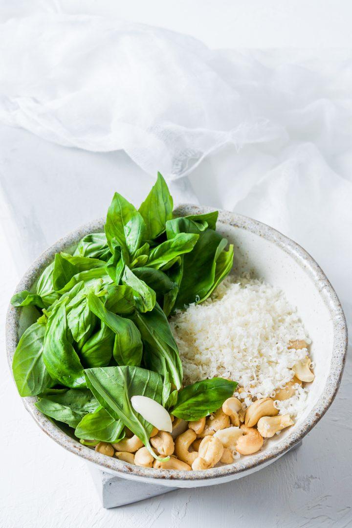 Ingredients for basil pesto with cashews, basil, grated parmesan and garlic