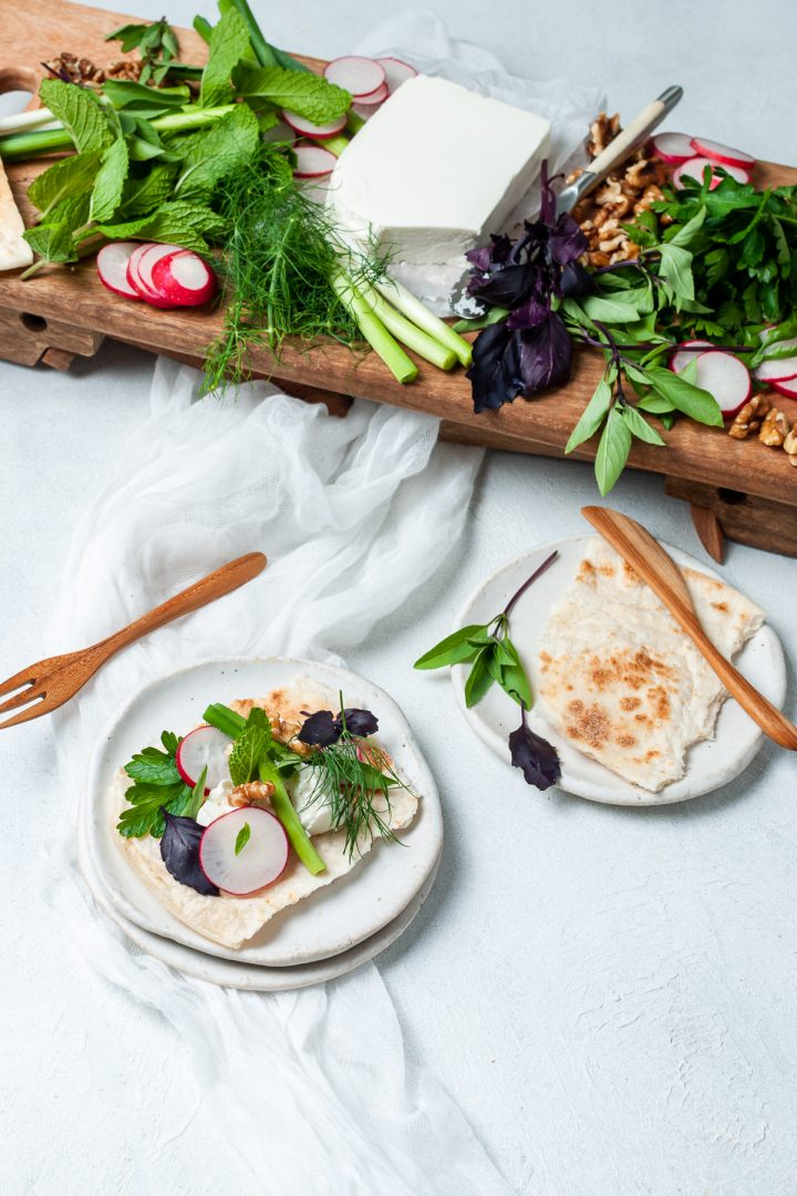 The platter being served: two plates showing a piece of flatbread on one plate and on the other, the flatbread topped with feta and fresh herbs