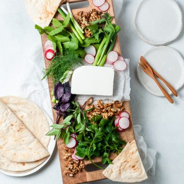 overhead photo of the ingredients on a wooden platter: feta, radishes, various fresh herbs, walnuts and flatbread