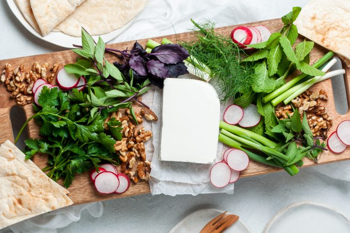 overhead image of the feta platter with a rectangle of feta cheese surrounded by fresh herbs, radishes, walnuts, and spring onions on wooden board