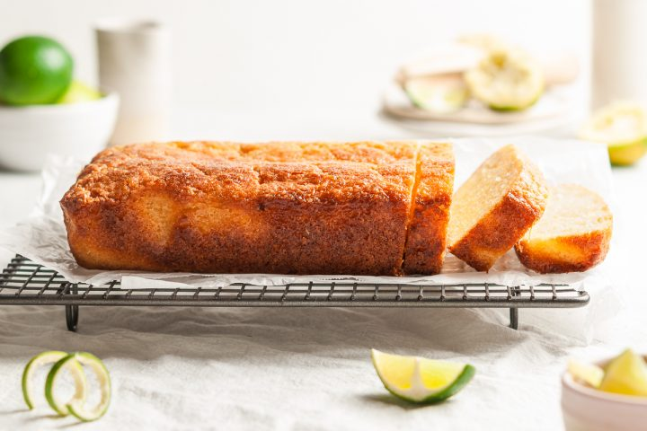 side view of lime drizzle cake with two cut slices about to fall on the right hand side
