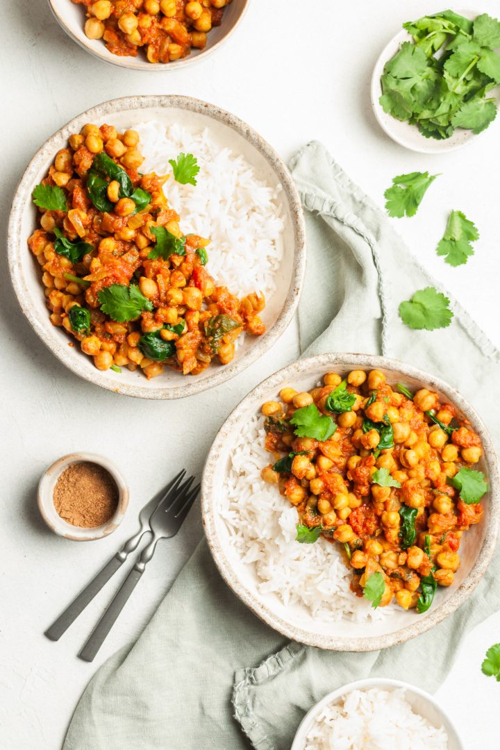 overhead photo of two bowls of vegetarian curry served with rice, with extra fresh coriander and garam masala to serve