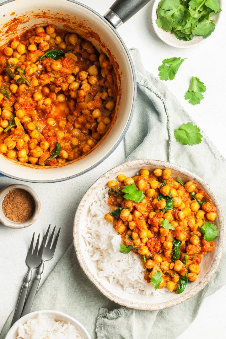 chickpea curry in a saucepan, some in a bowl with rice, just been served and ready to eat