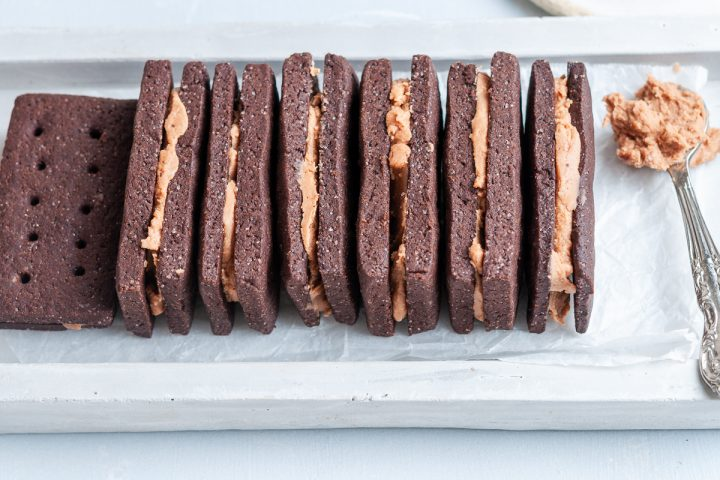 angled shot of bourbon biscuits stacked side by side with a spoon of chocolate buttercream to their right