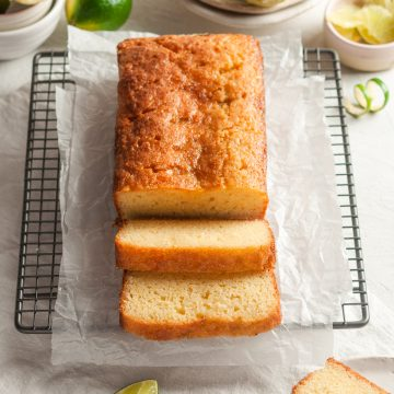 angled shot of lime drizzle cake to how shiny lime drizzle and cut slices to show soft texture