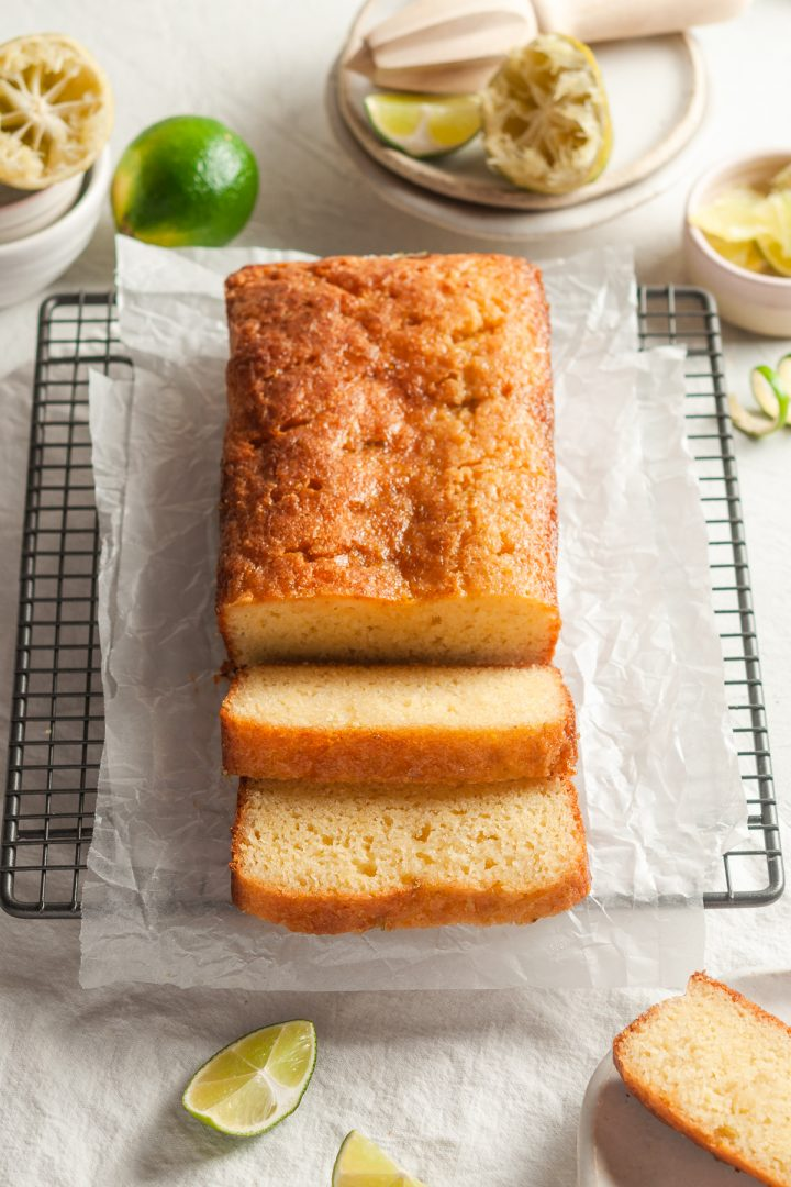 angled shot of drizzle cake to show shiny drizzle and two slices at the front to show fluffy texture of the cake