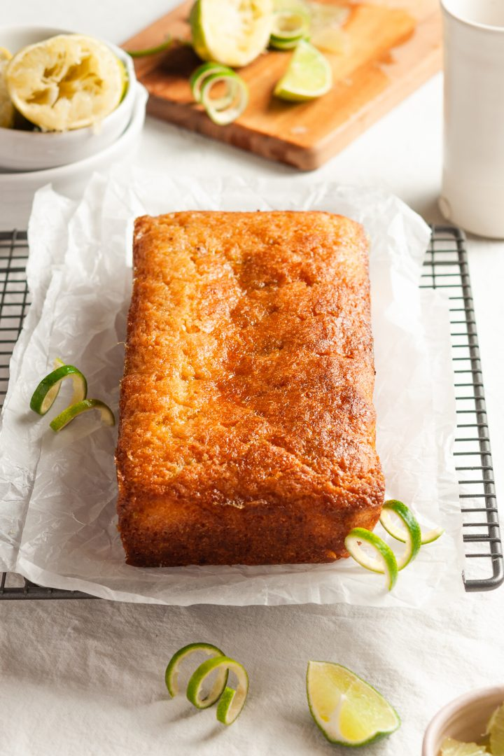 uncut lime drizzle cake, the lime glaze catching the light. Cut limes and lime zest are dotted around the cake