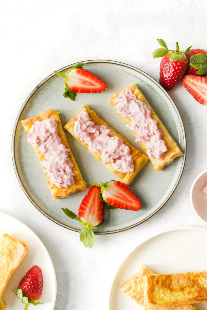 overhead shot of baby french toast with ricotta and strawberries on plate, served with extra fresh strawberries
