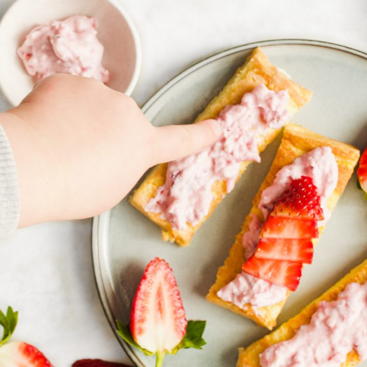 toddler hand pointing to a finger of french toast, about to pick it up and eat it