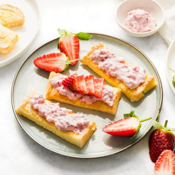 strawberry ricotta spread on french toast sticks on a plate, with extra strawberries dotted around