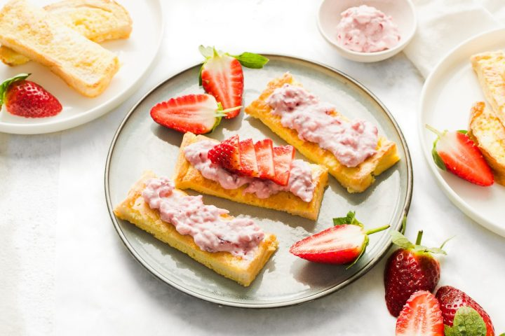 angled shot of 3 sticks of french toast on plate topped with ricotta and sliced strawberries, other sticks of toast just visible