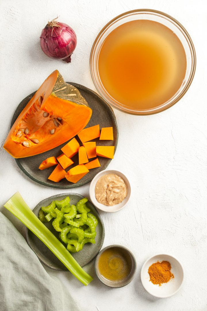 ingredients for pumpkin soup laid out individually, in bowls, the celery and pumpkin chopped to show the size of the pieces required for this recipe
