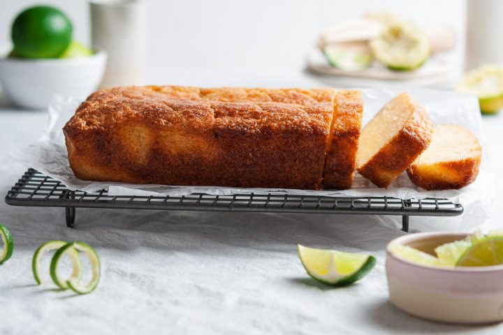 side view of lime drizzle cake on a wire rack, with 3 slices cut