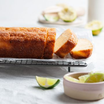 close up of a sliced lime drizzle cake on cooling rack, slices of lime positioned around the cake