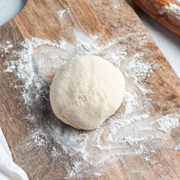 ball of yeast free pizza dough on floured wooden board ready to be rolled out and topped with pizza toppings