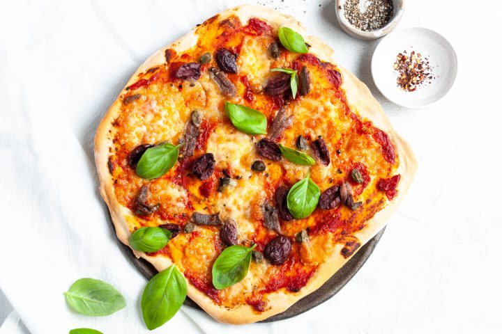 Pizza puttanesca sprinkled with basil leaves