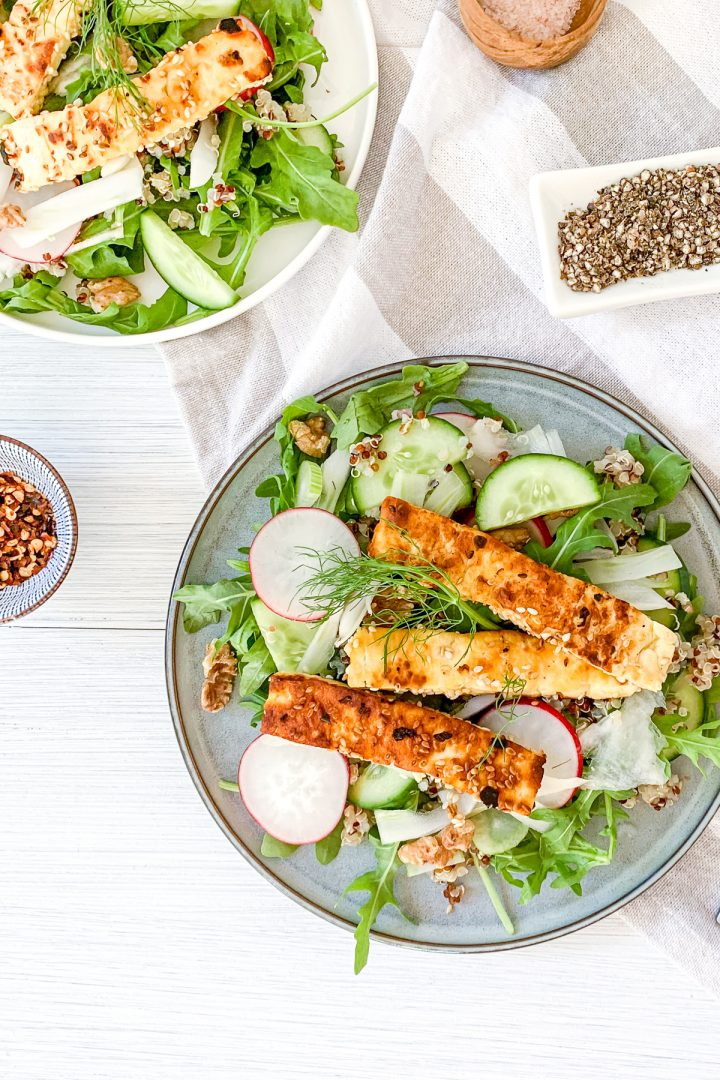 overhead photos of two plates of quinoa halloumi salad ready to eat, extra chilli flakes and black pepper for sprinkling