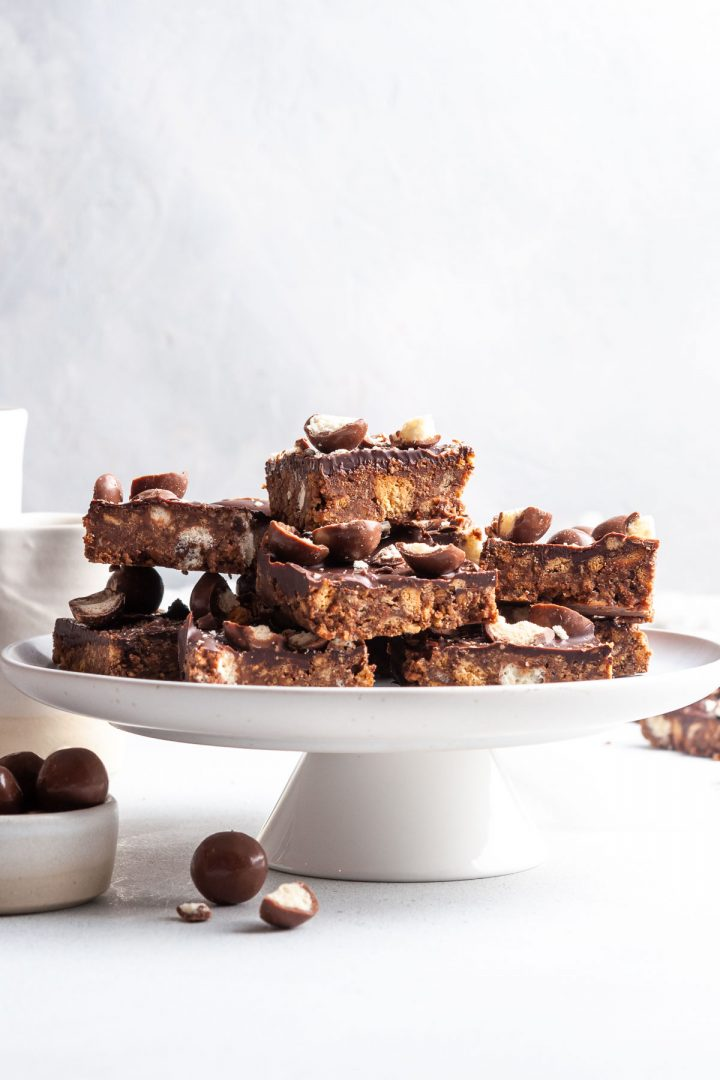a pile of cut squares of Maltesers tray bake slice on a plate ready to serve