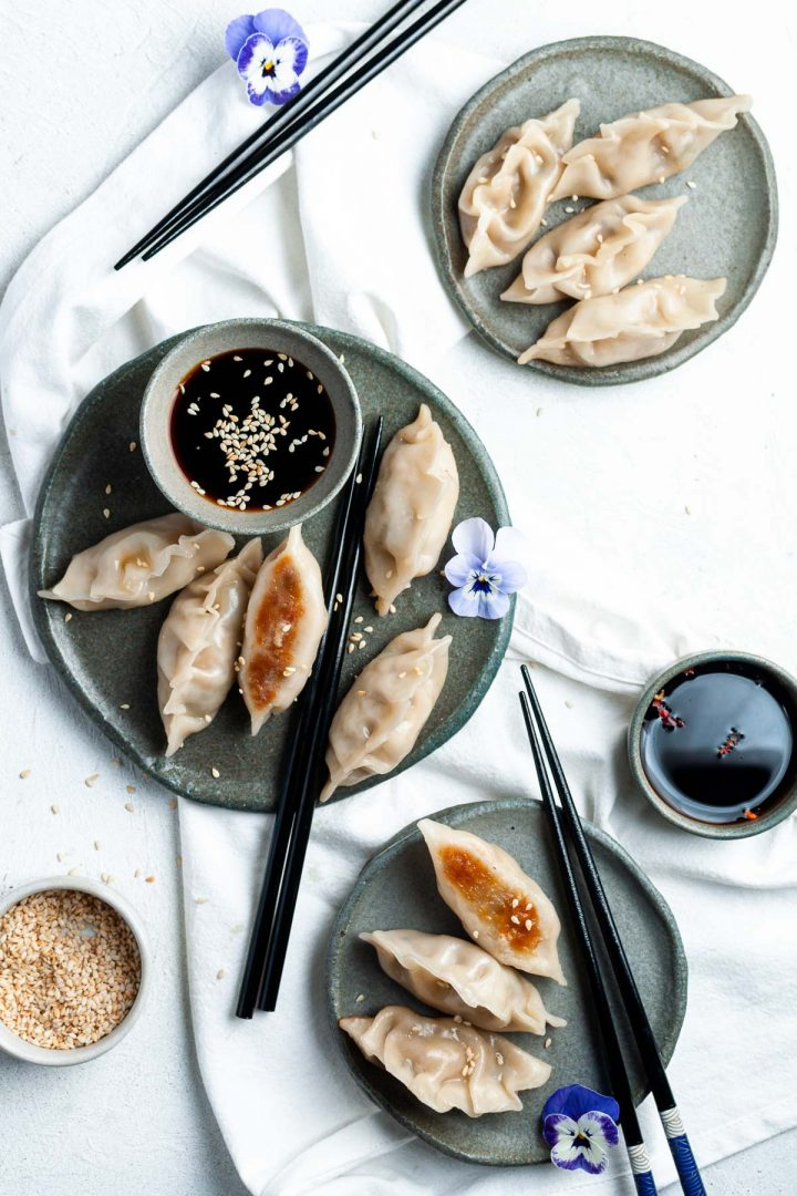 3 plates of vegetarian mushroom potstickers, one larger plate with a bowl of traditional gyoza dipping sauce, a small bowl of chilli dipping sauce is to the left of a smaller plate. Purple pansies add a splash of colour