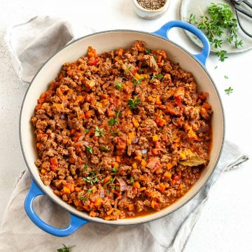 Cooked savoury mince in a blue pan topped with fresh herbs, ready to eat
