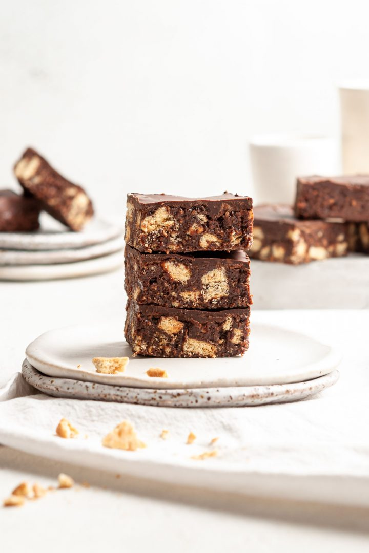 side view of a stack of 3 squares of hedgehog slice, other squares just visible behind, to show the crunchy biscuit pieces and chocolate top