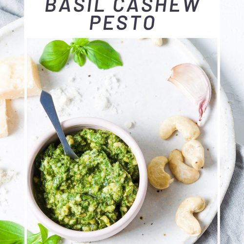 pin for basil cashew pesto showing the pesto in a pink pot, cashew nuts and basil leaves scattered around