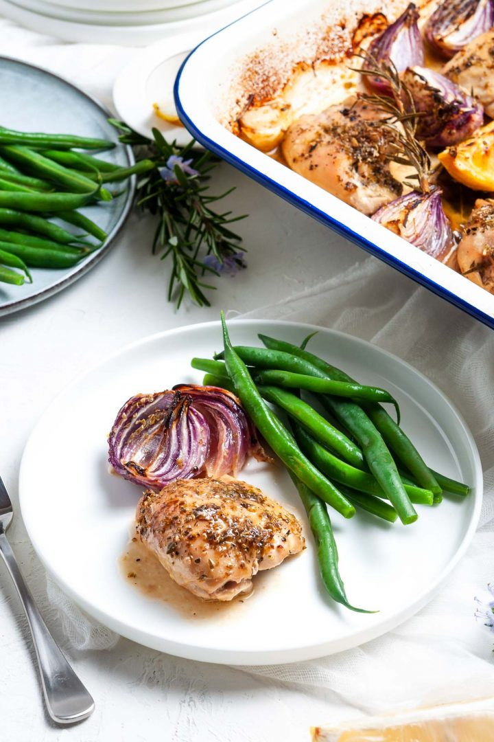 A baked chicken thigh on plate served with green beans and a baked red onion, the tray bake just visible behind