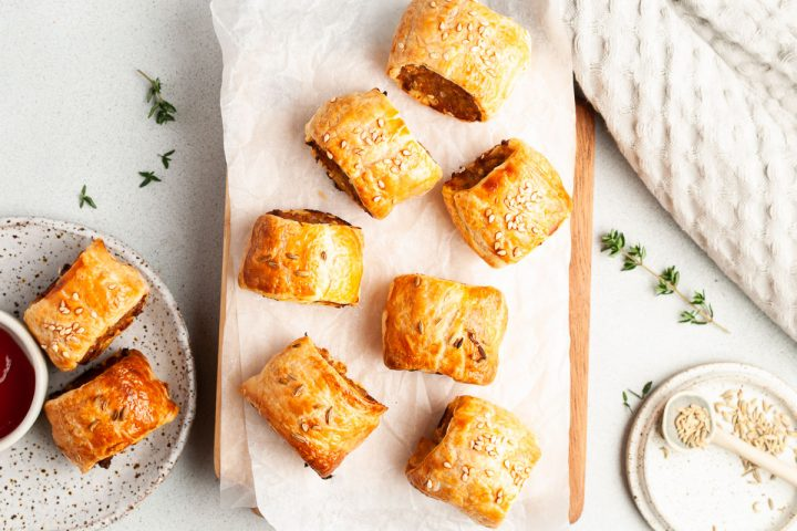 golden baked sausage rolls laid out on paper on a wooden chopping board ready to eat, fresh thyme sprinkled around