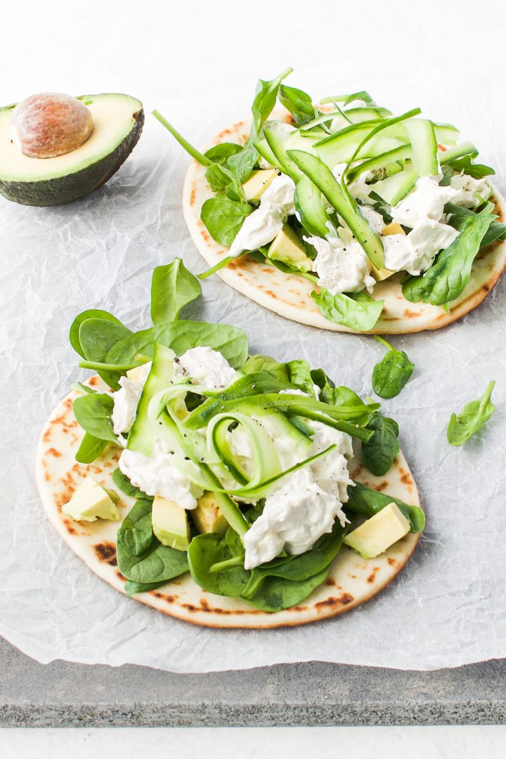 two naan breads topped with spinach, cucumber, avocado and chicken salad. Half an avocado just visible in the background
