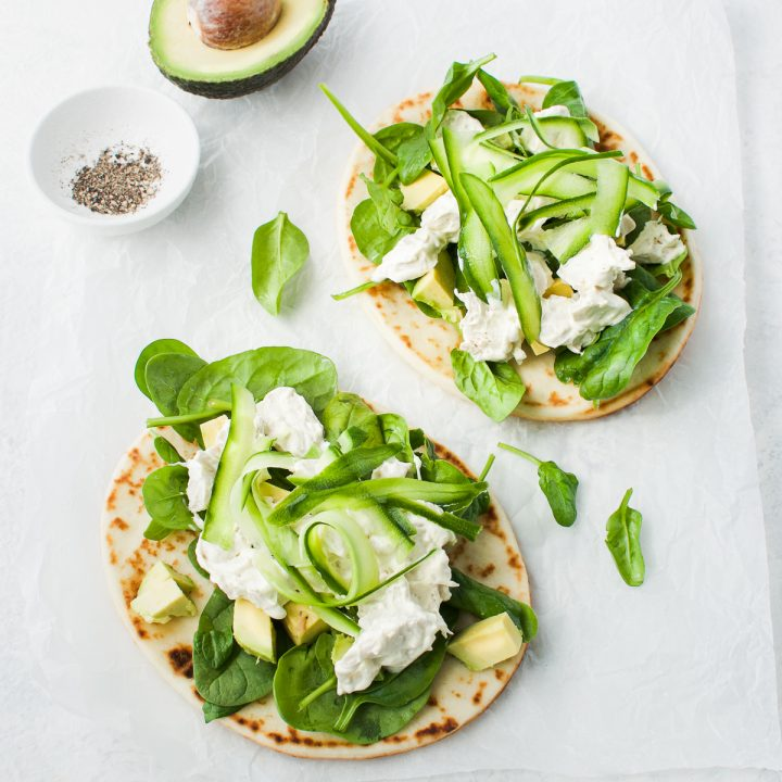 overhead shot of two naans topped with leftover chicken salad, half an avocado and extra black pepper on the side ready to serve