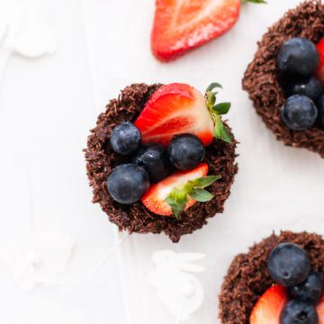 overhead photo of a chocolate shredded wheat nest filled with blueberries and cut strawberries