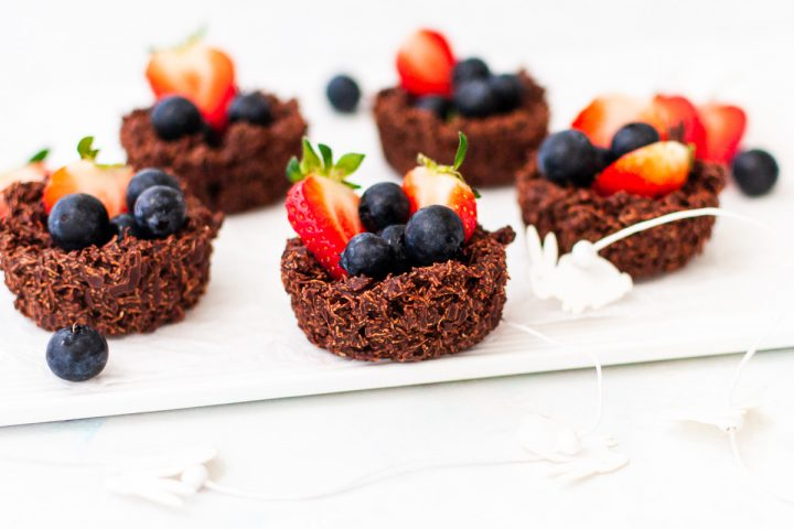 side view of shredded wheat nests filled with berries on a white background