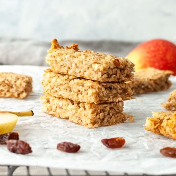 a stack of 3 pear flapjacks, with pear and raisins just visible