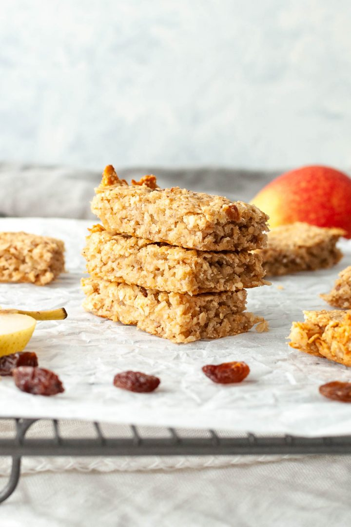 stack of 3 flapjack oat bars on cooling rack, surrounded by pear and raisins