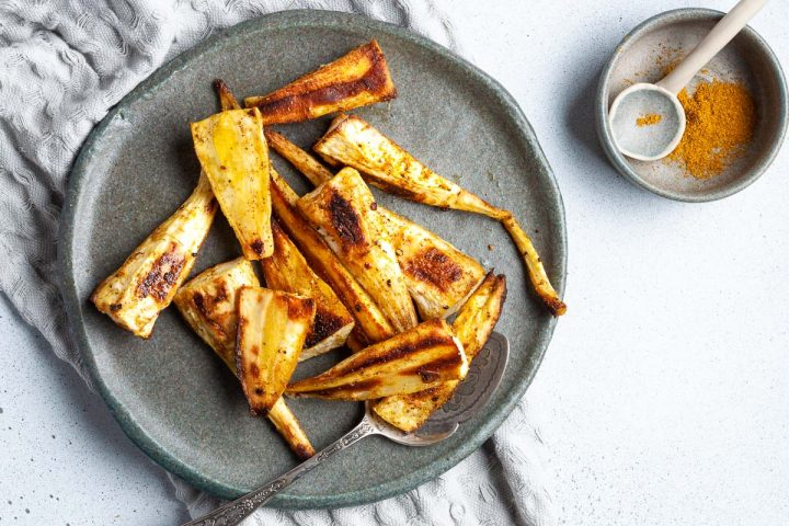crispy golden parsnips on a blue plate with a spoon ready to serve