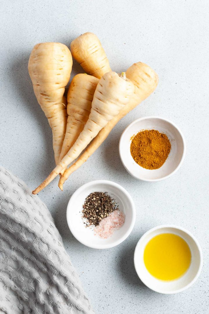 ingredients for roasting parsnips with curry powder laid out in individual bowls