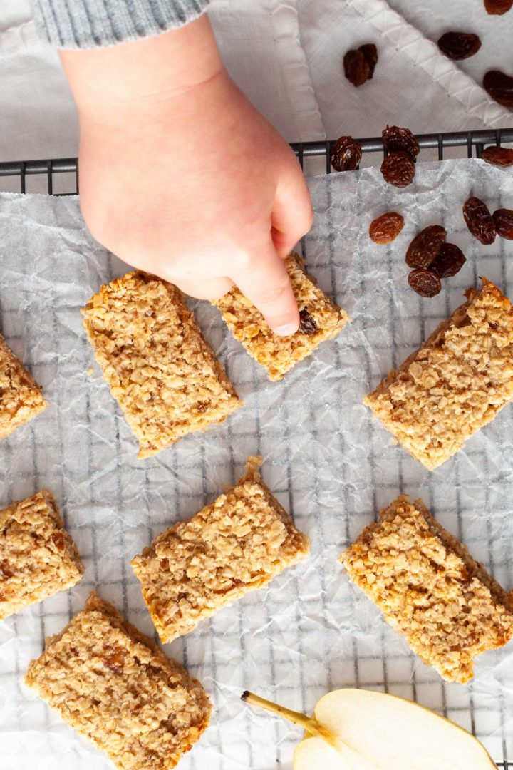 overhead photo of oat bars in a random pattern on a cooling tray, a babies hand pointing to one to show babies love these flapjacks!
