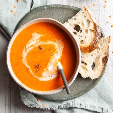 carrot red lentil soup in a bowl with a spoon in it, to show it being eaten. Two slices of sourdough are on the side ready to dunk in to it.