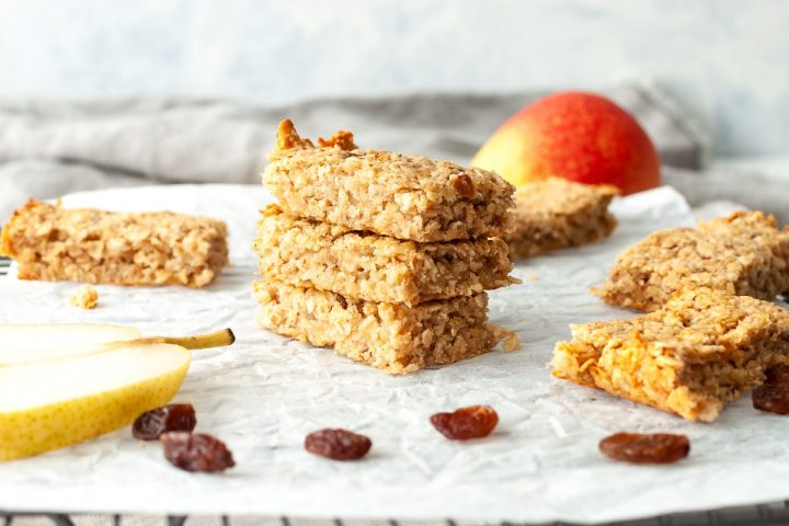 a stack of 3 flapjacks on white paper on cooling rack, surrounded by pears and raisins