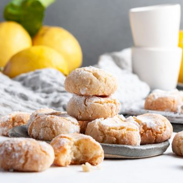 biscotti di mandorla on a dark blue plate, fresh lemons and white espresso cups just visible in the background